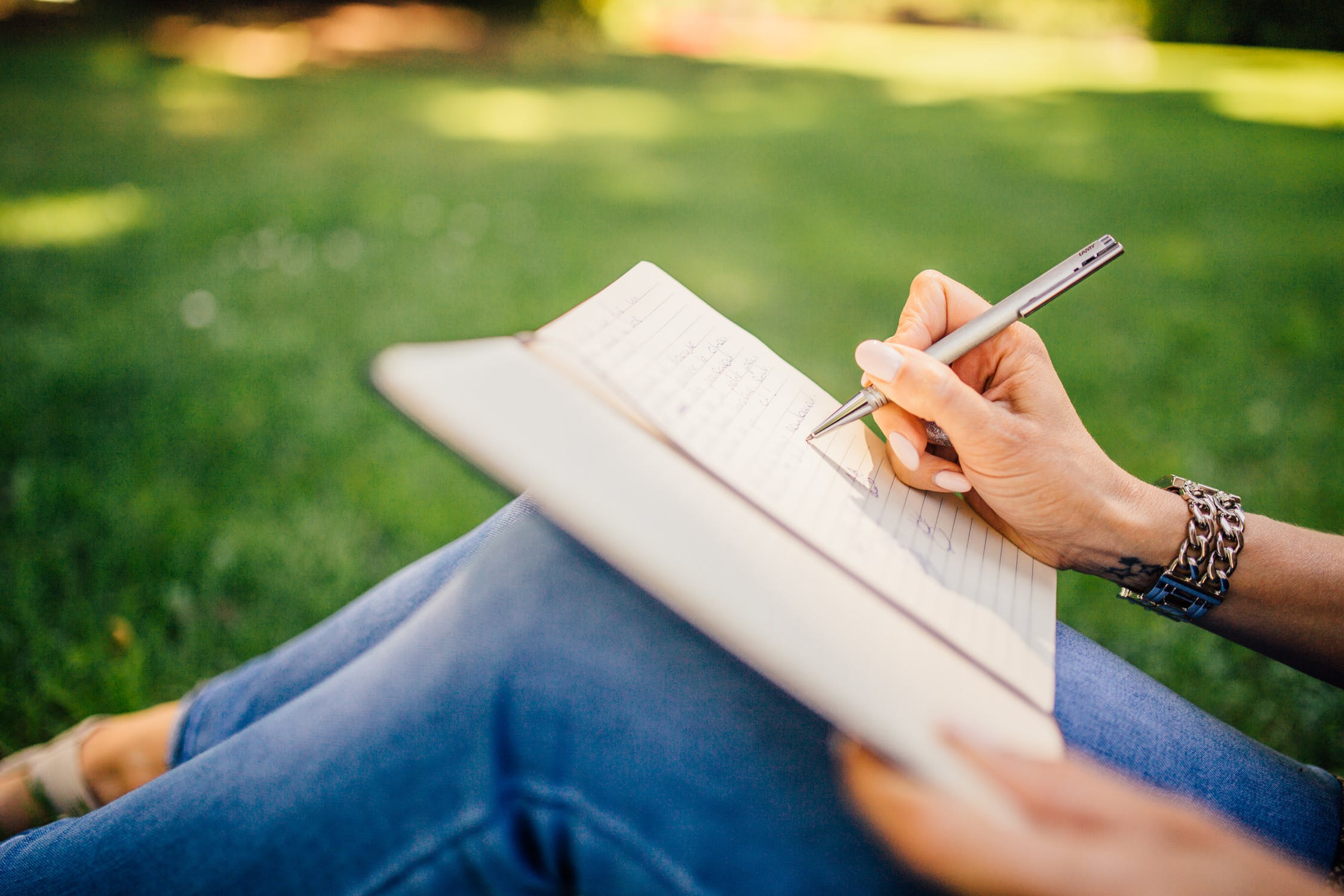 A woman writing down personal quotes about recovery in a journal