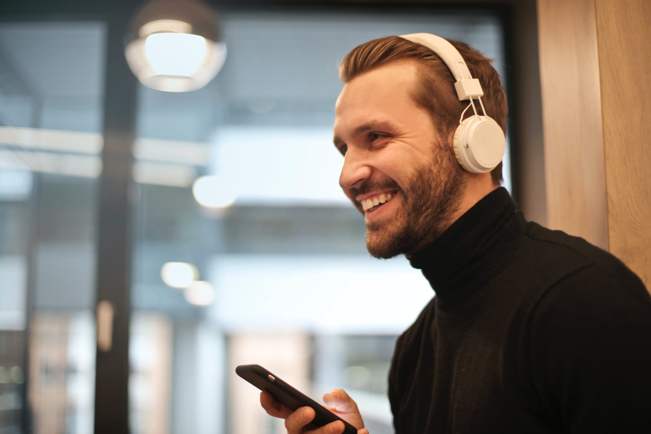 A man smiling while listening to a recovery podcast