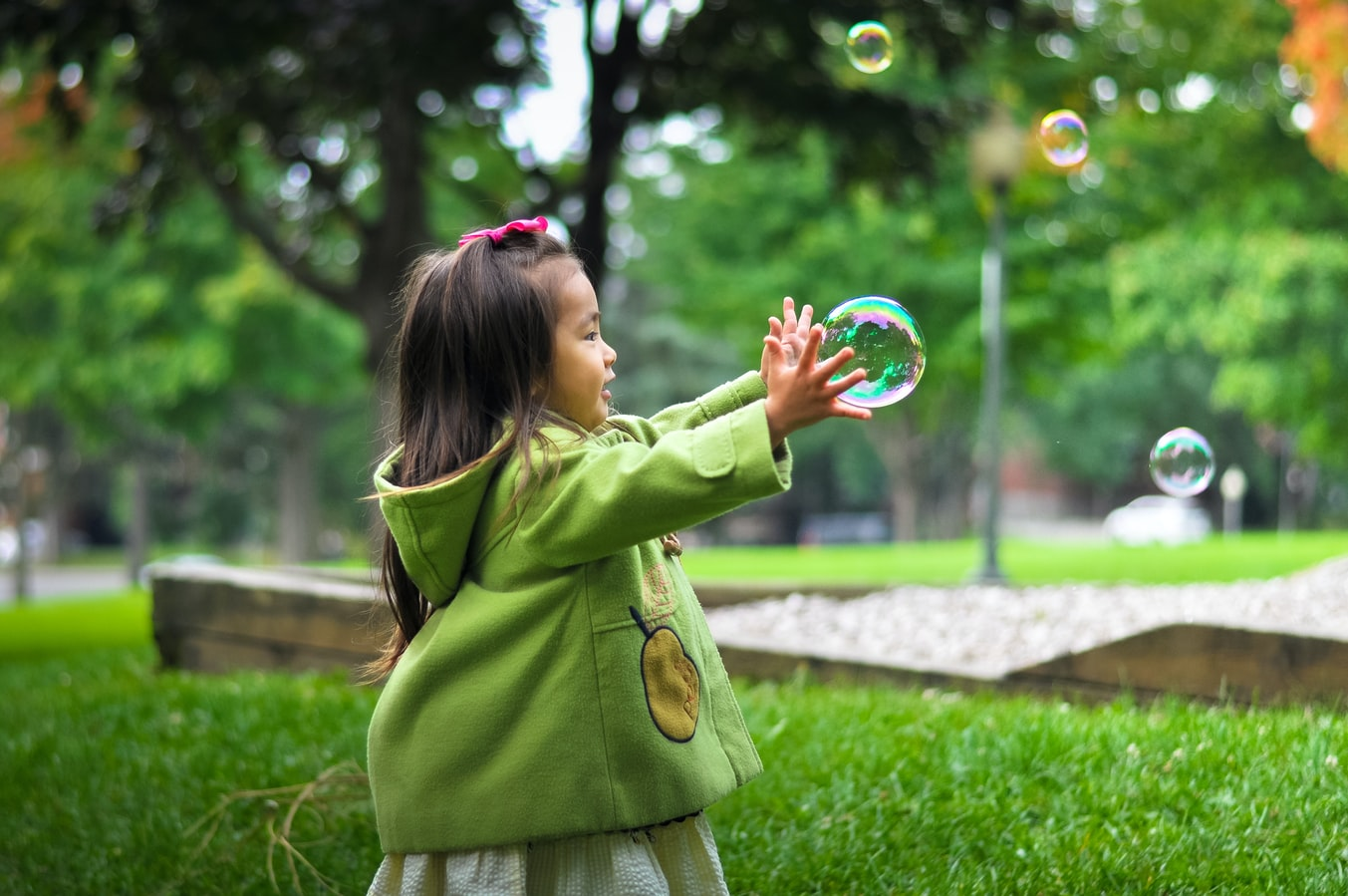 A young girl playing outside with bubbles. There are many children who experience adverse childhood experiences